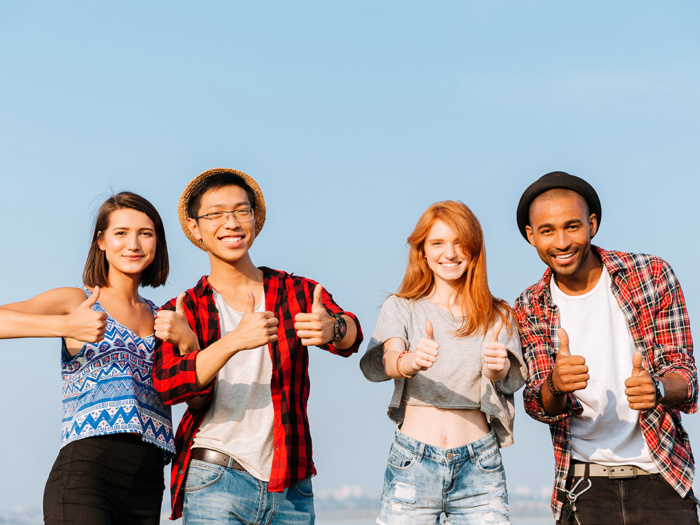 Graphicstock multiethnic group of smiling young friends standing and showing thumbs up over blue sky background Sd Hn Vlq Hne cropped small